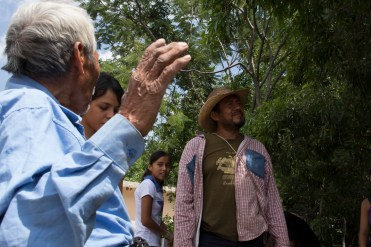 Un viejo habitante de la comunidad explica a un grupo de visitantes lo antiguo de la cultura que ahí se mantiene.