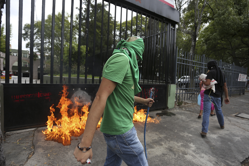 Normalistas rociaron con gasolina y prendieron fuego a la valla metalica de la secretaría de finanzas del Estado