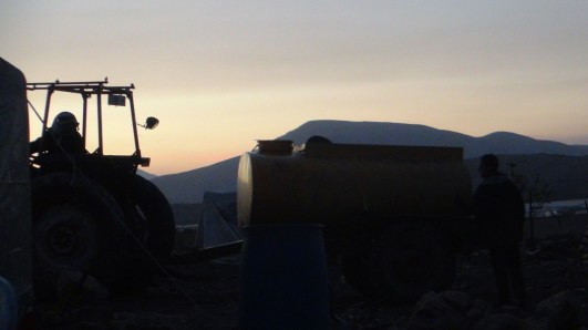 El muhktar Abdel Rahim Basharat recibe el tanque de agua en el atardecer. Fotografía: Susana Norman