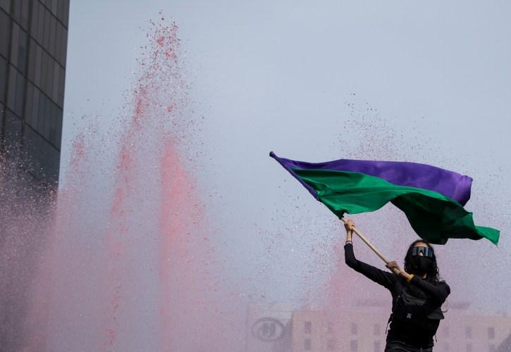 Durante las movilización del 8 de marzo en Ciudad de México, una mujer con el rostro y los brazos cubiertos ondea una bandera morada y verde sobre la Fuente del Caballito.