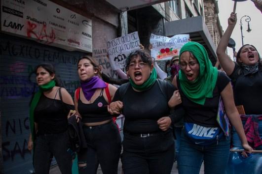 La marcha avanza sobre 5 de febrero. Un grupo de mujeres se agarran de los brazos como si fueran un bloque o una cadena humana. Mientras caminan y se sostienen entre ellas, gritan consignas para entrar a la plancha del Zócalo.