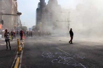 """Durante toda la marcha policías de la Ciudad de México, usaron extintores con gases contra las manifestantes. En diversos momentos, se vieron policías vestidos de civil dándoles órdenes para disparar los gases, en esta foto se observa a uno de ellos en el Eje Central a un costado de Bellas Artes junto a la consigna """"«La policía no me cuida»."""