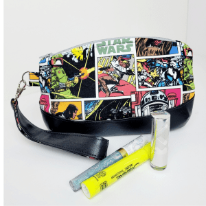 Full image of wristlet clutch with retro star wars fabric and marine vinul featuring props