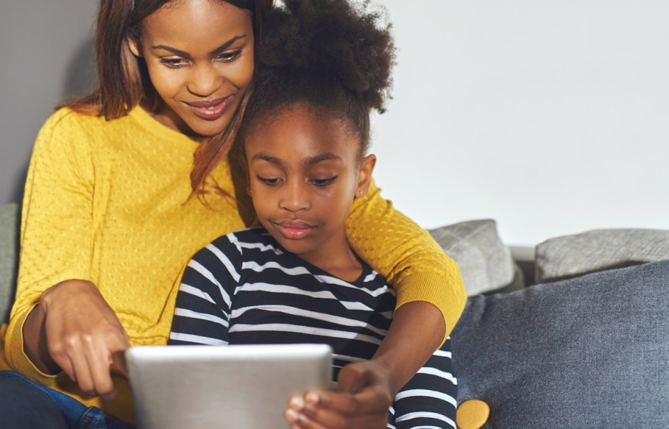 Black mom and daughter learning on tablet sitting at home in sofa