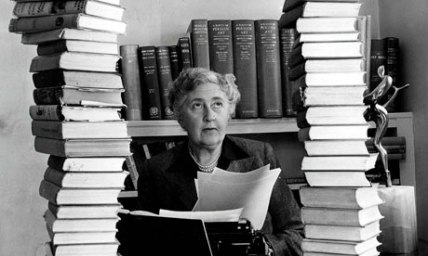 Agatha Christie at her desk, between two piles of books