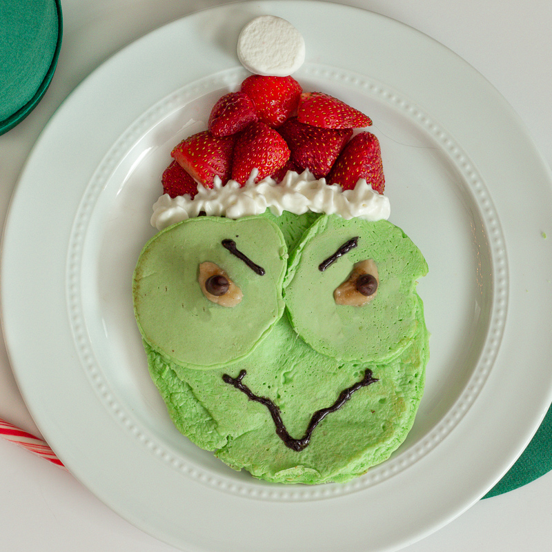Green The Grinch Pancake with whipped cream and strawberries.