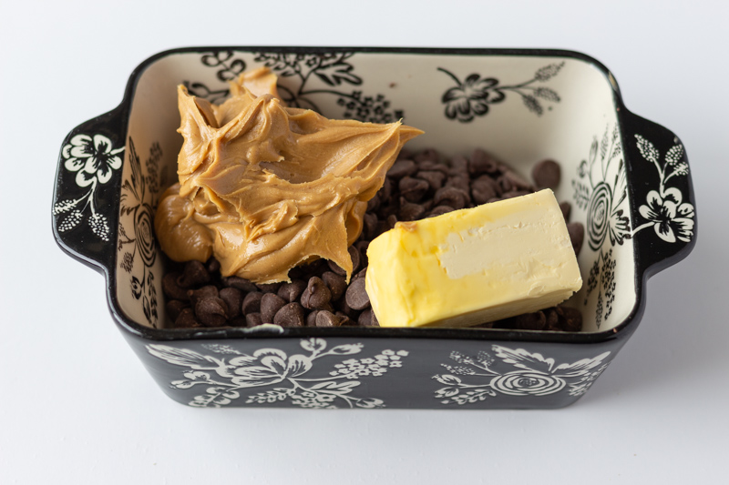 Peanut butter, chocolate chips, and softened butter in a microwave safe bowl.
