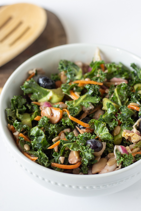 Kale salad in a white bowl next to a wooden spoon.