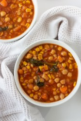 Two bowls of Moroccan soup with a white dish towel.