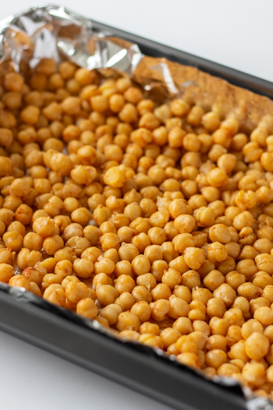 Chickpeas with paprika and cumin on a baking sheet.