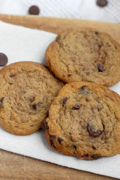 Three chocolate chip cookies on a white paper towel.