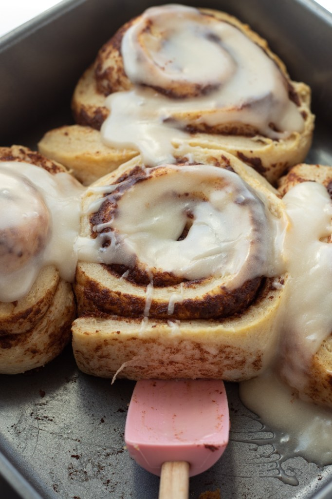 Pink spatula scooping up cinnamon roll.