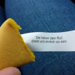 A fortune cookie, cracked open, with a fortune written in German visible.