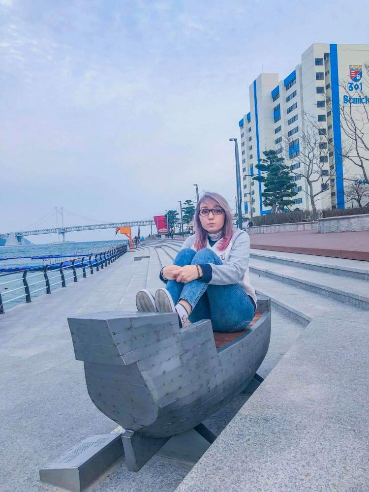 a girl with the pink hair sitting on the bench near the bridge , Busan, South Korea