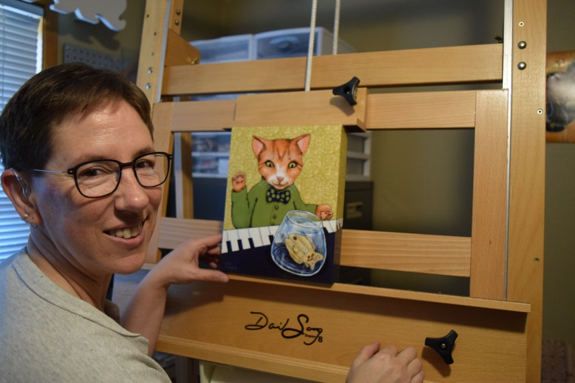 """Sue Clancy putting one of her recent artworks on the new easel """"to see how it'd work""""."""