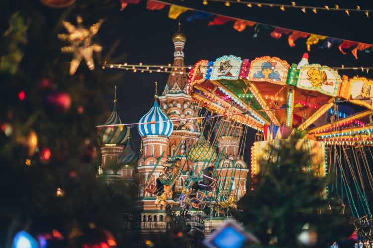 colorful carousel against cathedral on red square at new year night