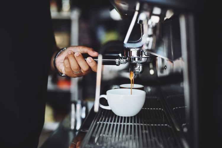 close up of hand holding coffee machine