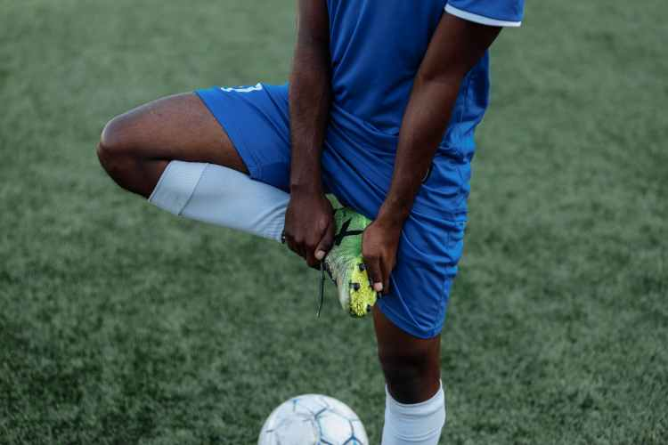 man in blue and white jersey shirt playing soccer