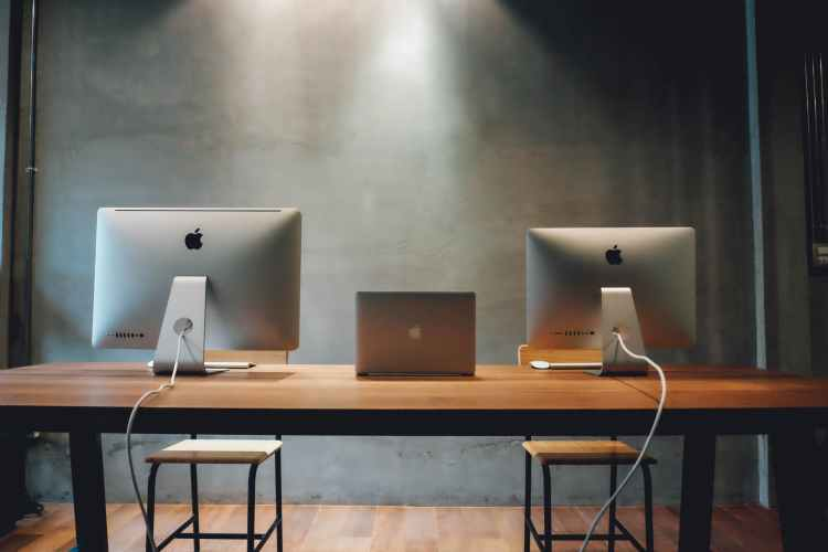 two silver imac on table