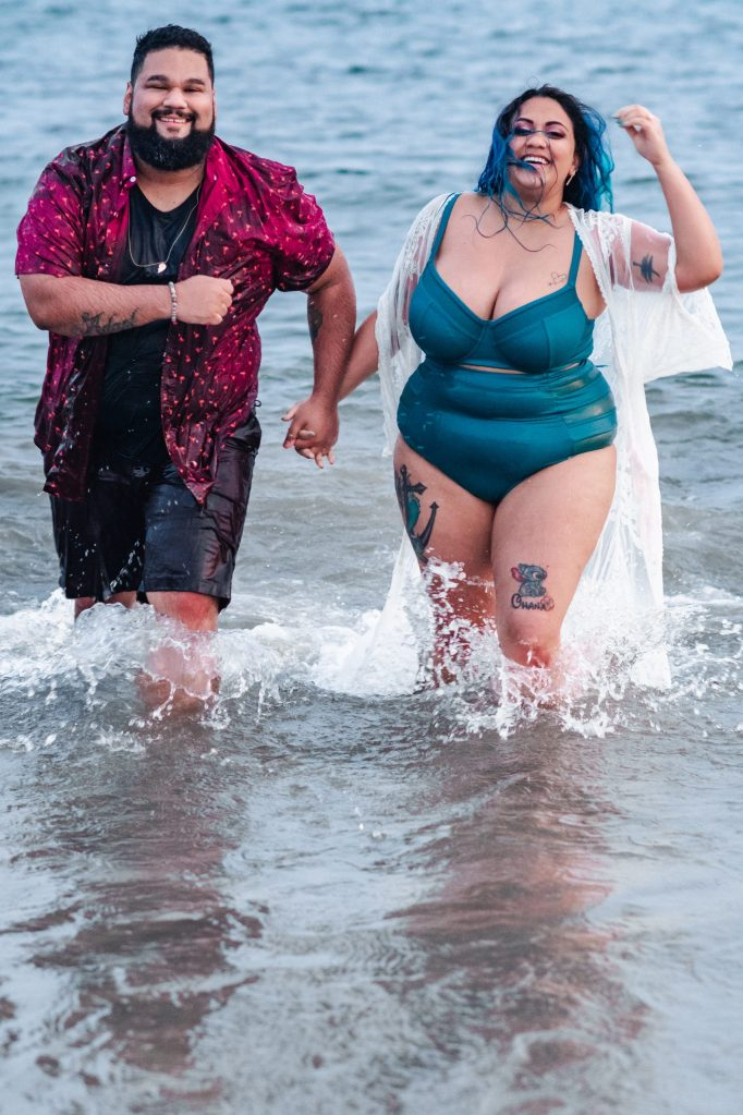 plus-size-curvy-couple-running-through-beach-suessmoments
