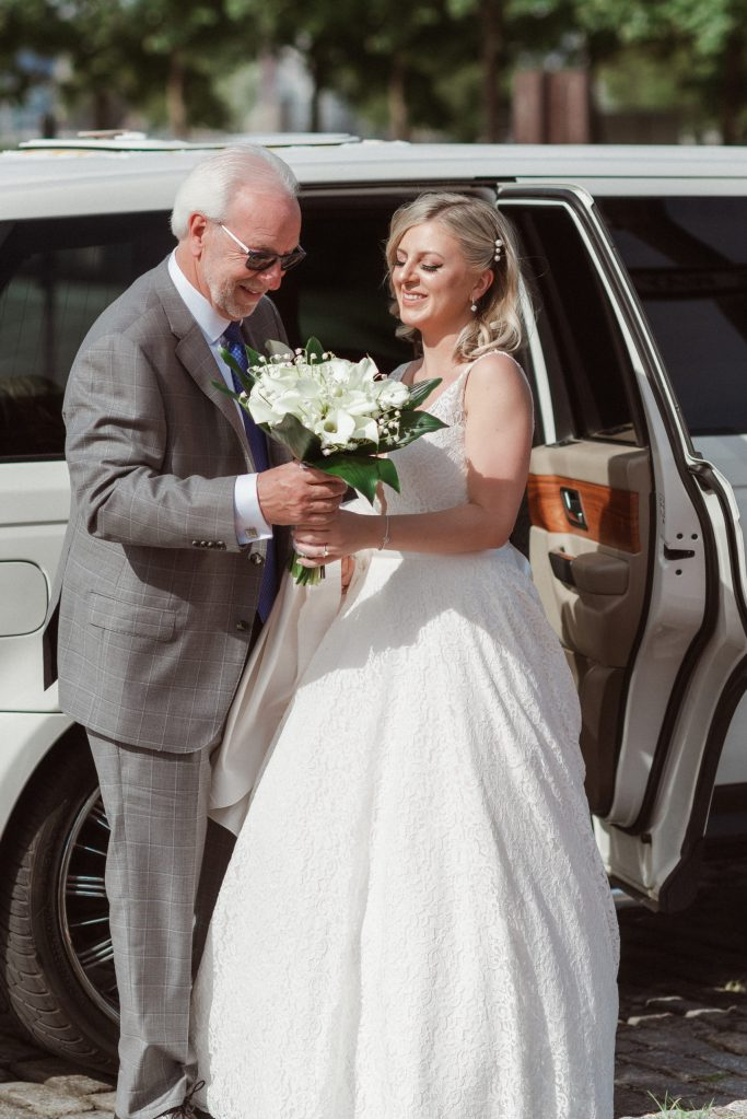 father-of-bride-helping-bride-out-of-limo