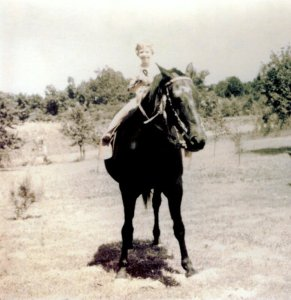 Sue, age 5 or 6, astride Dan the plow horse