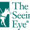 The Seeing Eye with a dog in harness Guiding someone who is blind