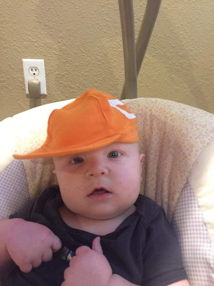 Baby Aiden Leonardo wearing an orange hat