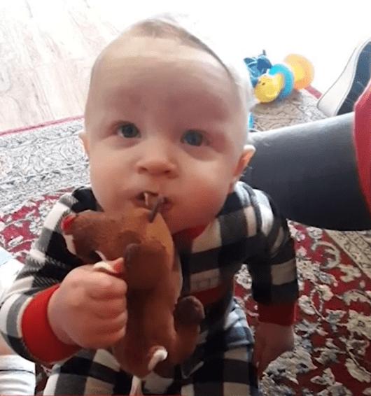Baby Aidan Leonardo wearing checkered pajamas and holding a stuffed toy