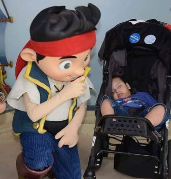 Josias Marquez asleep in his stroller with a character from Jake and the Neverland Pirates