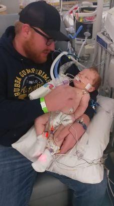Adam McKinney holding injured son Dawson
