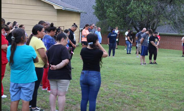Mourners lower their heads in prayer for Frankie Gonzales