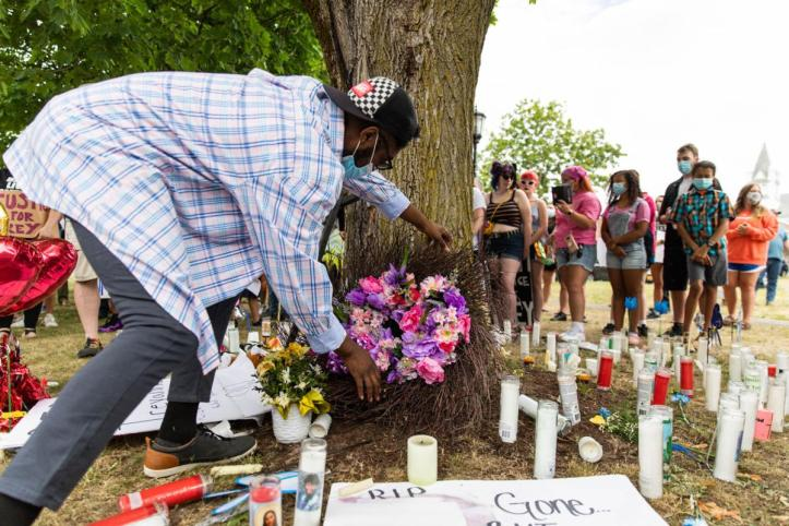Isiah Samuels places a wreath on Treyanna Summerville's memorial