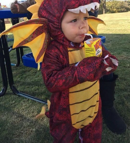 Stetson Blackburn dressed as a dragon for Halloween, drinking a juice box
