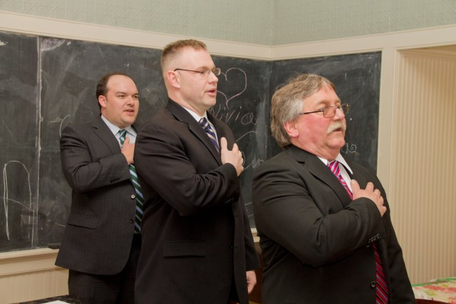 (L-R) Greenport Village Trustee Doug Roberts, Trustee and Deputy Mayor Jack Martilotta and Mayor George Hubbard recite the pledge of allegiance at Monday's meeting (Credit: Paul Squire).