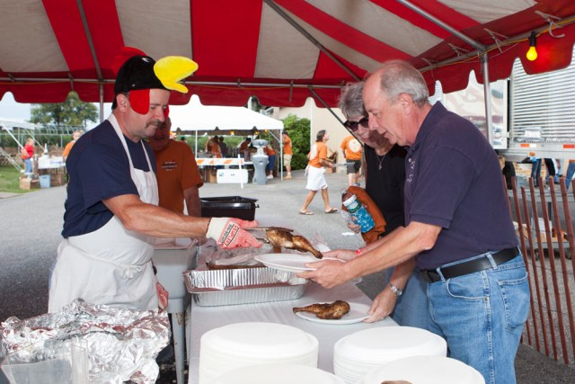 Wearing his traditional chicken hat, Tom Shelby serves Larry and Pat Speciner of Middle Island. (Credit: Katharine Schroeder)