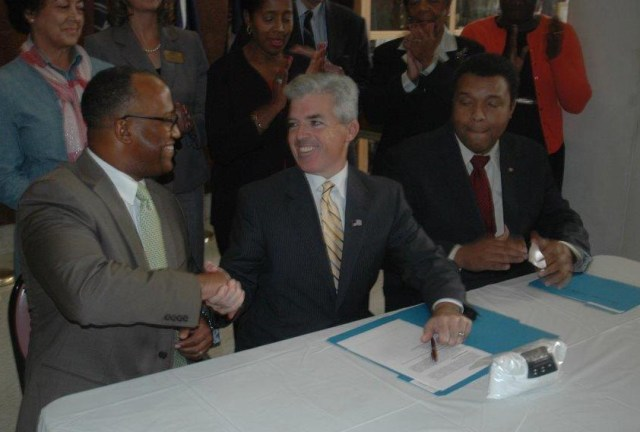 Suffolk County Legislature Presiding Officer DuWayne Gregory, left, and County Executive Steve Bellone shake hands after the law is signed. (Credit: Courtesy)