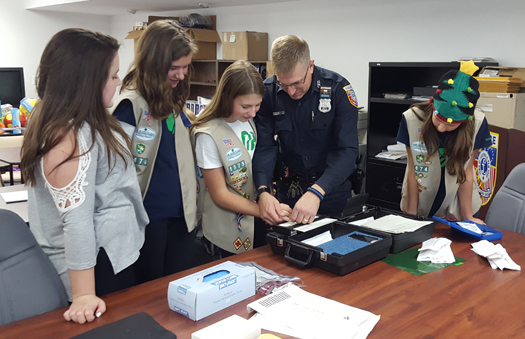 Girl Scout Ainsley Brewer gets fingerprinted by Southold police officer Bill Brewer as Delaney Hudock, Emily Nicholson and Sidney Brewer watch. The Cadettes were working on their Secret Agent badge. (Courtesy photo)
