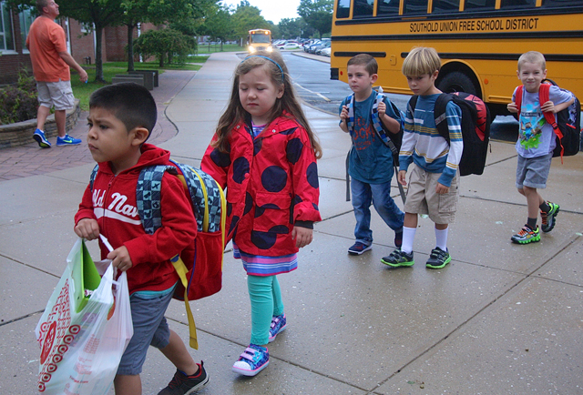 A group of somber kindergartners get off one of the buses first.