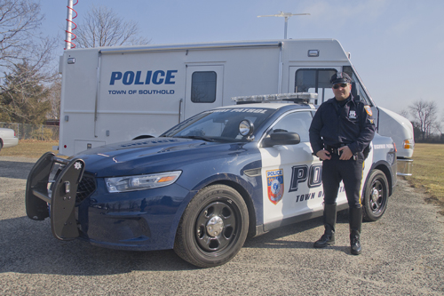 Highway patrol officer Peter Onufrak stands in front of the department's new Police Interceptor cruiser.