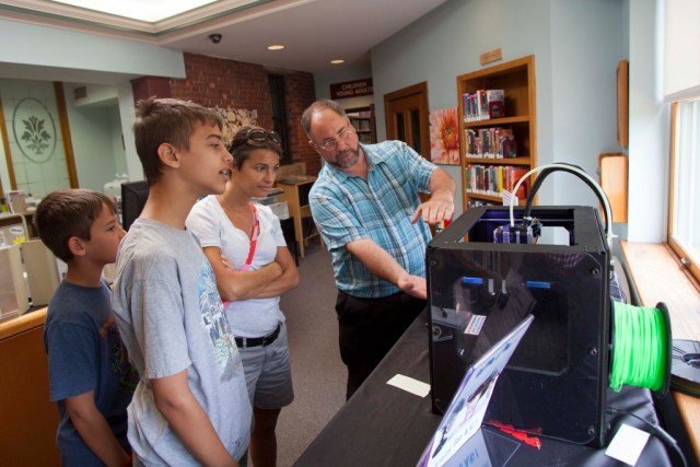 From left to right: Hunter Magnuson, 10, Ethan Magnuson, 12, and Kea Magnuson learn about the 3-D printer from library network administrator David Van Popering. (Credit: Chris Lisinski)