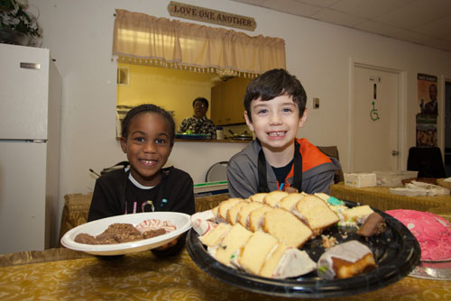Darlene Shelby, 4, and Jonah Conologue, 7, getting dessert ready for a Martin Luther King Jr. Day celebration in Greenport. (Credit: Katharine Schroeder photos)
