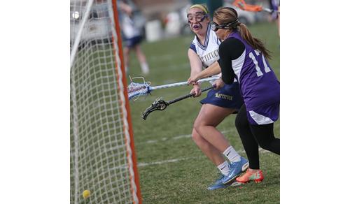 Mattituck/Greenport/Southold's Molly Kowalski gets off a shot despite the efforts of Hampton Bays' Paula Cardenas. (Credit: Garret Meade)