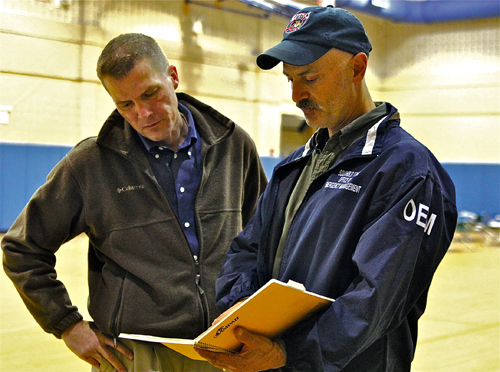 JENNIFER GUSTAVSON FILE PHOTO   Supervisor Scott Russell confers with town emergency coordinator Lloyd Reisenberg at the Mattituck High School storm shelter during Hurricane Sandy.