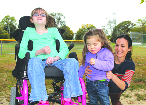 CARRIE MILLER PHOTO | Rachel Garms, 11, of Southold with Maren DeSantis, 2, and Maren's mother, Lena, of Mattituck at Tasker Park in Peconic last Saturday. The two girls met for the first time during October, Rett Syndrome Awareness Month.