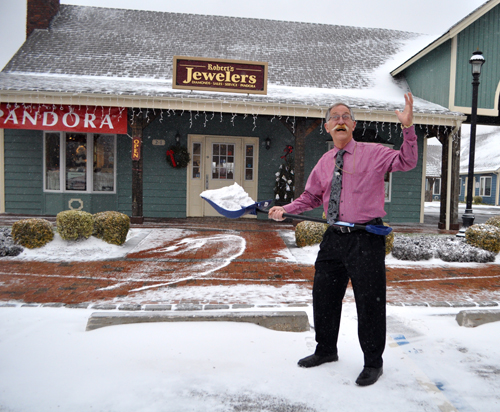 RACHEL YOUNG PHOTO | Robert's Jewelers owner Robert Scott, snow shovel in hand, at his Southold store Thursday morning.