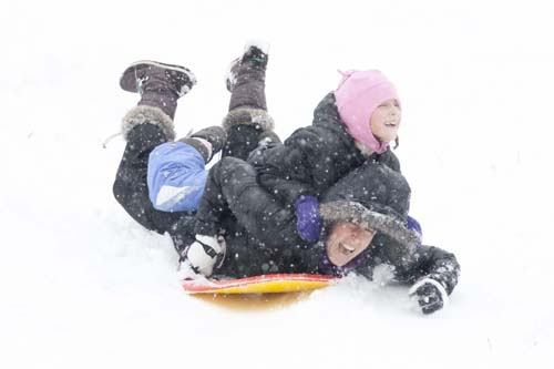 KATHARINE SCHROEDER PHOTO | Seven-year-old Bailey Shannon of Cutchogue hitches a ride atop her mom at the sledding hill in Mattituck.