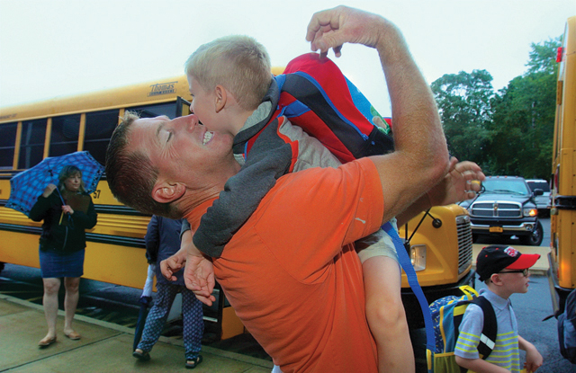"""Robert Bohn raced to school to greet his son Hudson, 6, as he excited the bus. """"I can't believe you are a first grader, aren't you excited.?"""""""