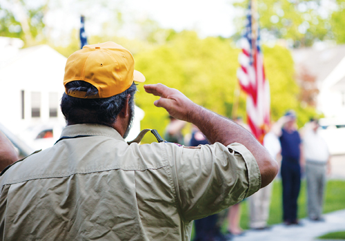 A man salutes the flag at a Southold Town Memorial Day parade. (Katharine Schroeder file)