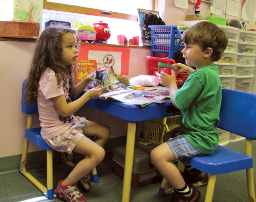 CYNDI MURRAY PHOTO  |  Two children read magazines at the Perry day care center in Greenport Friday.